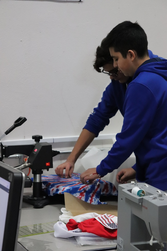 Students prepare design on shirt for the heat press